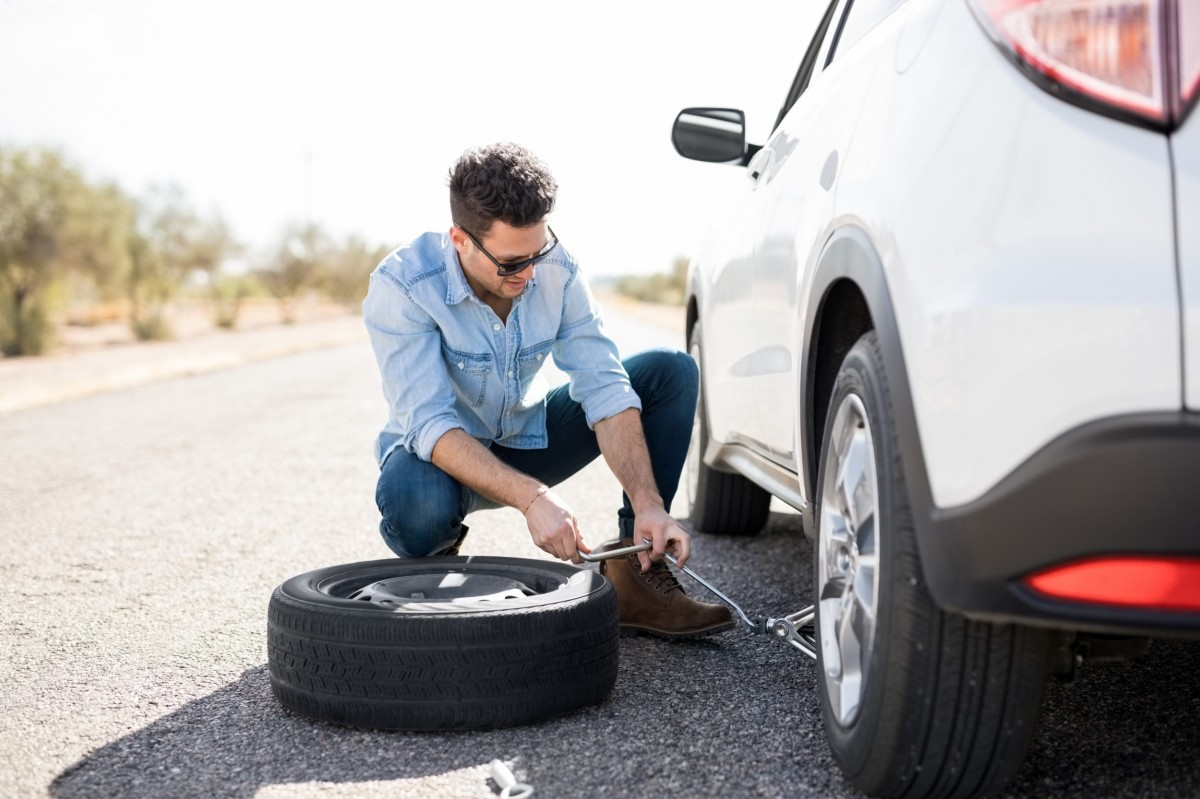 man changing a tire on side of road